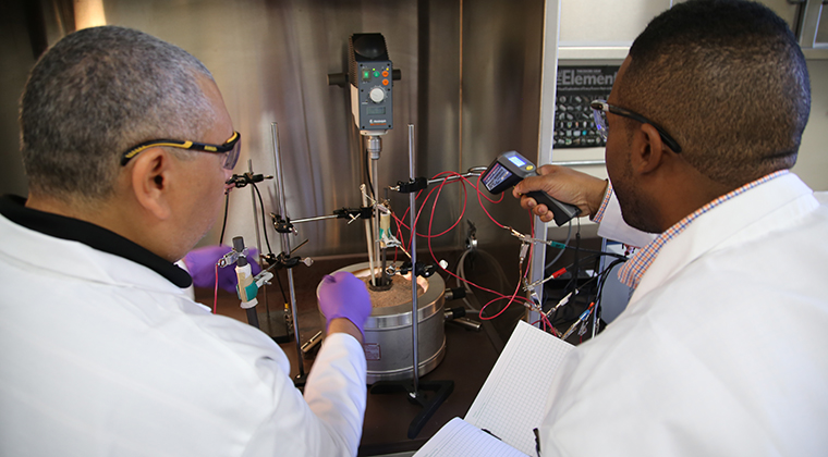 Hassan Elsentriecy, left, and Telpriore Tucker of MetOxs, take a voltage reading from a bench-scale test reactor running an electrodeposition process using molten salt to extract silver from ore. Photo credit: Paul Tumarkin/Tech Launch Arizona